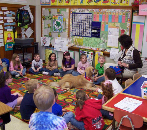 Second Grade classroom with kids in circle. A counselor is speaking about the dog in the middle of the circle.