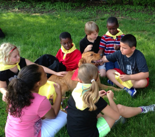 Kids surrounding and petting a dog in the grass