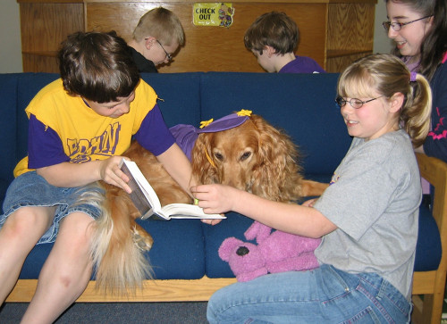Children reading to their therapy dog, Allie.