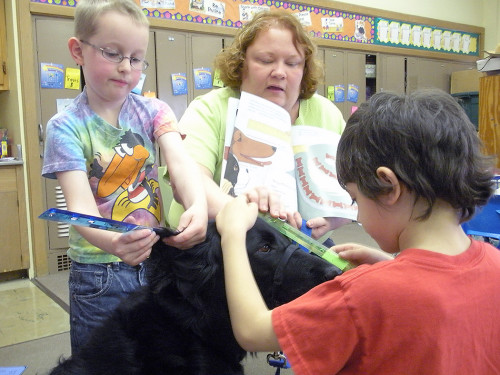 Children and teacher measuring a dog's head with a ruler.