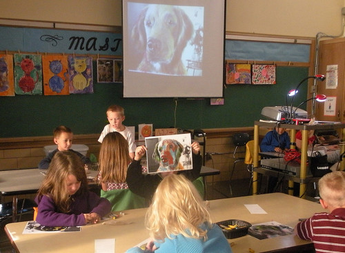 Children drawing picture of dog's head from an overhead projection.