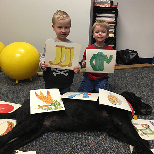 Picture of two boys (students) showing their artwork. More artwork lays on top of Kramer who is sprawled in front of them.
