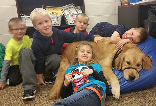 Photo of school kids laying in a heap with Lansbury the dog.
