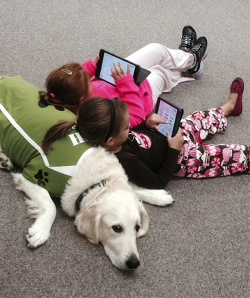 Kids leaning against Brewster playing on their laptops.